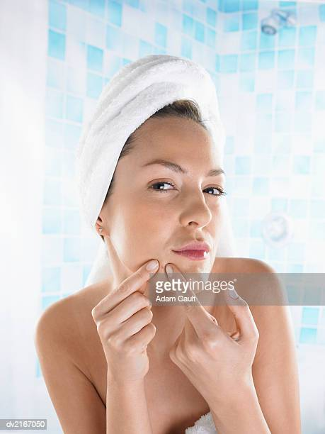 Woman Squeezing a Pimple on Her Chin
