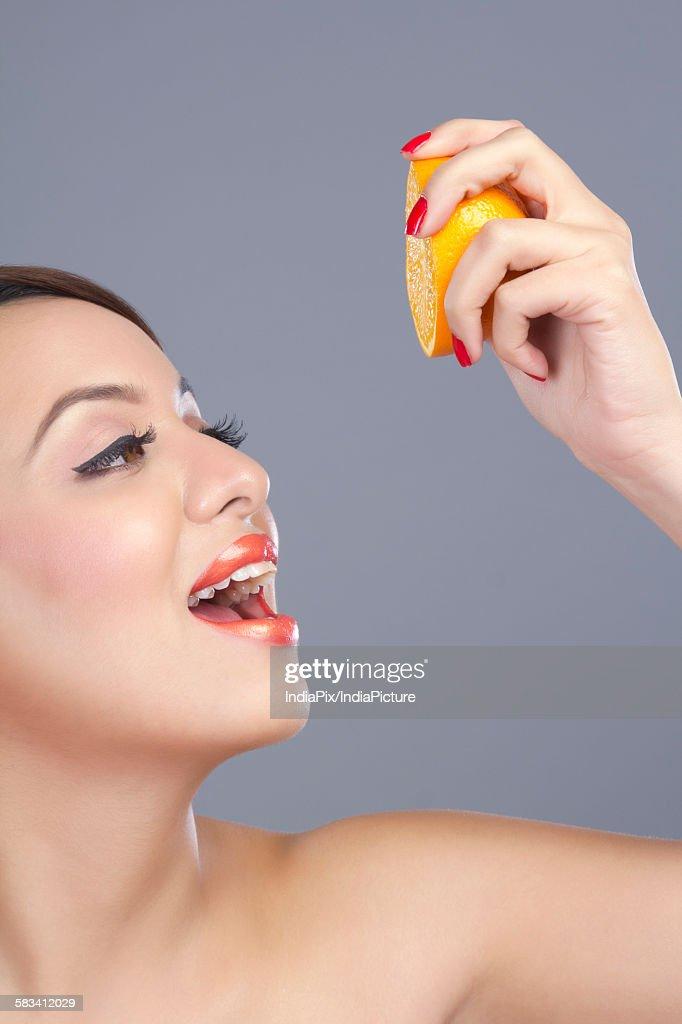 Woman squeezing an orange : Stock Photo