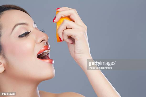Woman squeezing juice from orange into her mouth