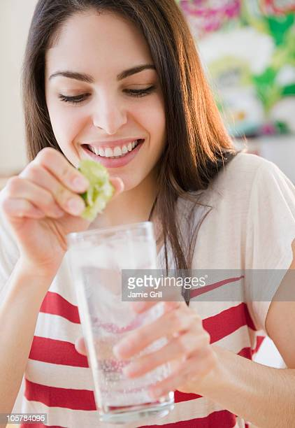 Woman squeezing lime into water