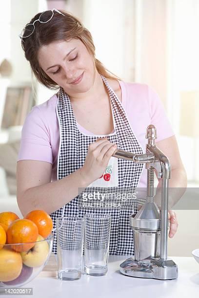 Woman squeezing orange juice in kitchen