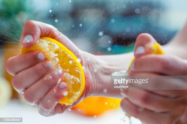 woman squeezing the juice from a lemon. - squeezing stock pictures, royalty-free photos & images