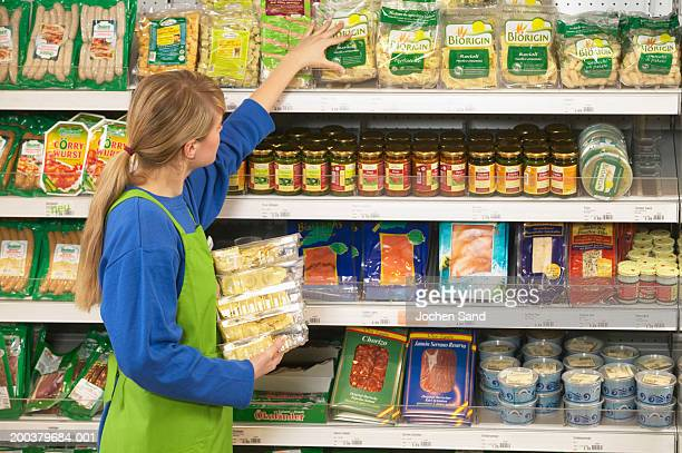woman stacking shelves in supermarket - stacking stock pictures, royalty-free photos & images