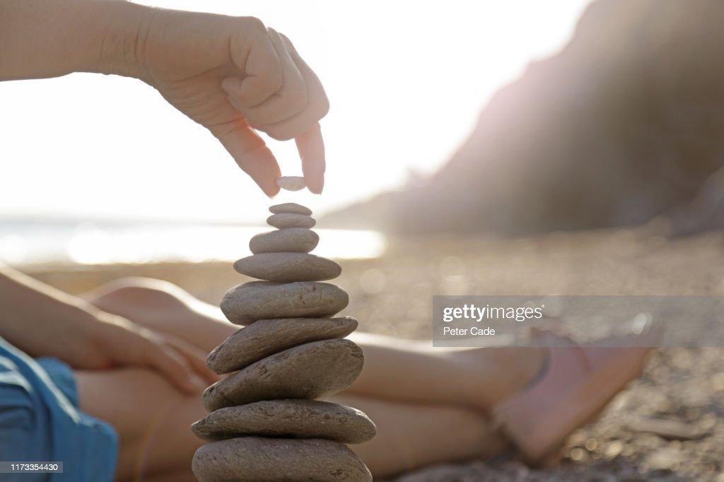 Woman stacking stones on beach : Stock Photo