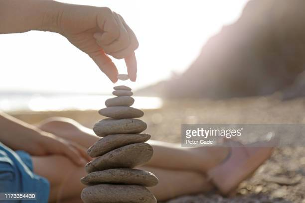 woman stacking stones on beach - vacations stock pictures, royalty-free photos & images