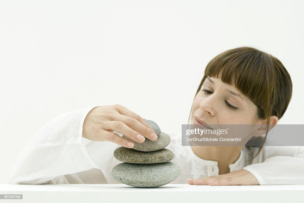 Woman stacking stones : Stock Photo