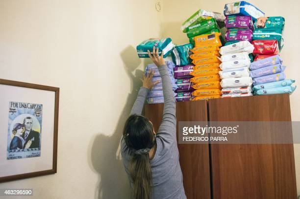 A woman stacks diapers on top of a wardrobe in Caracas on February 2 2015 The shortage of food and different products in Venezuela has worsened in...