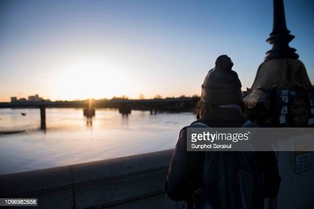 a woman stand on a bridge watching winter solstice sunrise over river thames in london - fulham stock pictures, royalty-free photos & images
