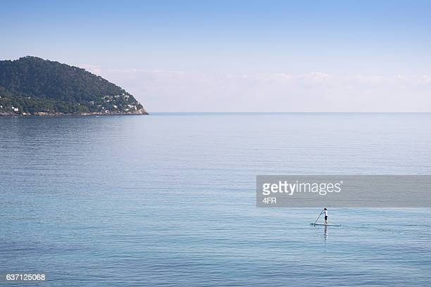 Woman Stand Up Paddeling SUP in the wide calm Ocean