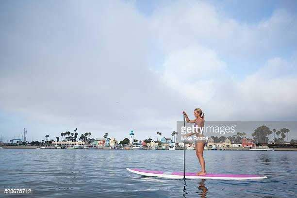 Woman stand up paddle boarding in Marina Del Rey, California, USA