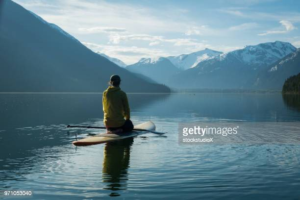 woman stand up paddle boarding on a pristine mountain lake - whistler british columbia stock pictures, royalty-free photos & images