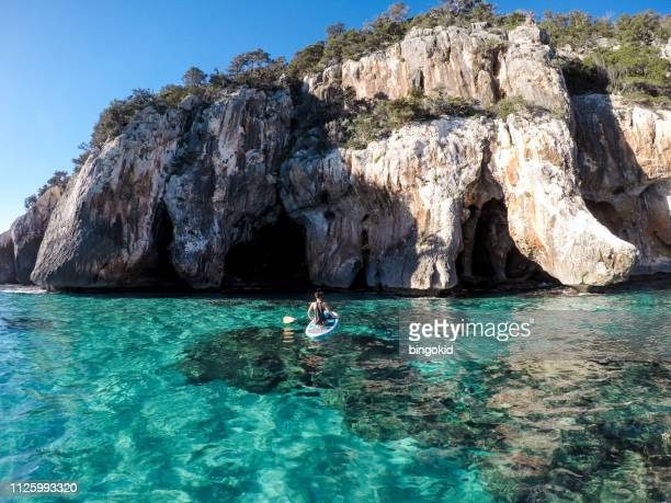 Woman stand up paddling towards cliffs and caves