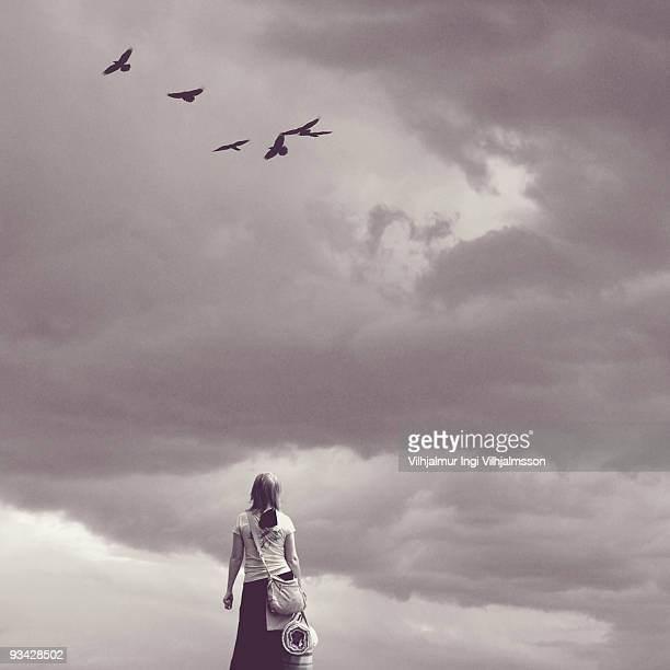 woman standing against a cloudy sky with ravens - crow bird stock photos and pictures