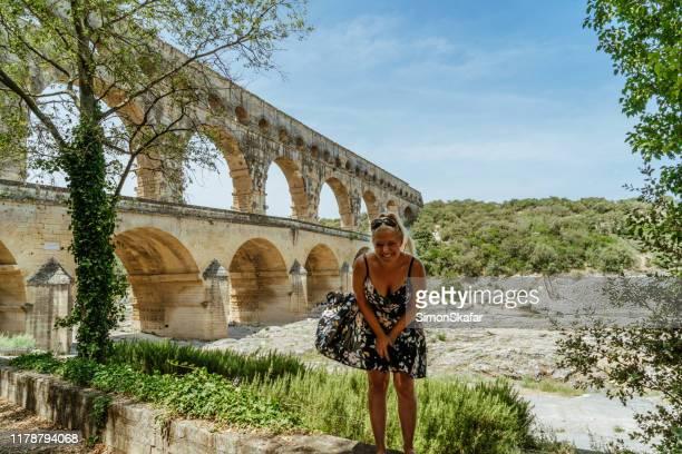 woman standing against aqueduct bridge and smiling at camera, vers-pont-du-gard, gard, france - pont du gard stock pictures, royalty-free photos & images