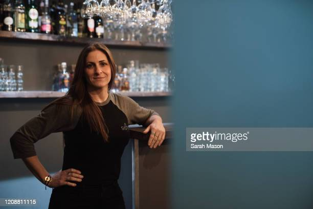 woman standing against bar looking at camera - industry stock pictures, royalty-free photos & images