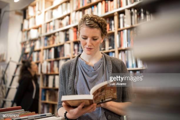 Woman standing against bookshelf reading book