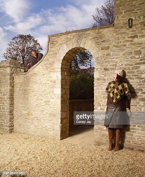woman standing against brick wall, man looking over wall - coneyl stock pictures, royalty-free photos & images