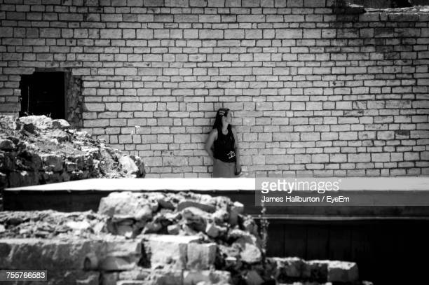 Woman Standing Against Brick Wall