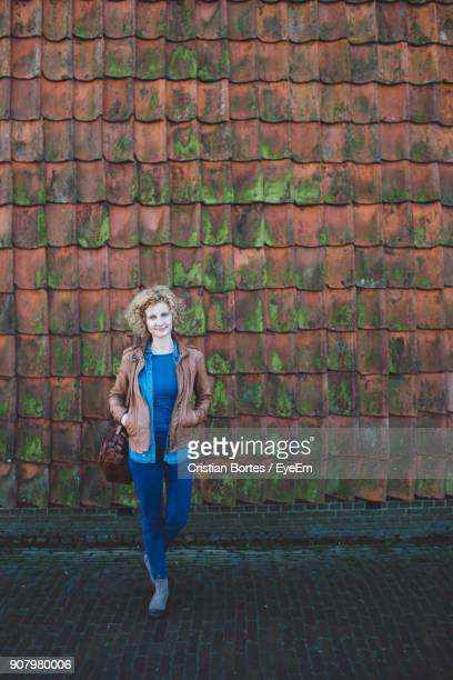 woman standing against brick wall - bortes stock pictures, royalty-free photos & images