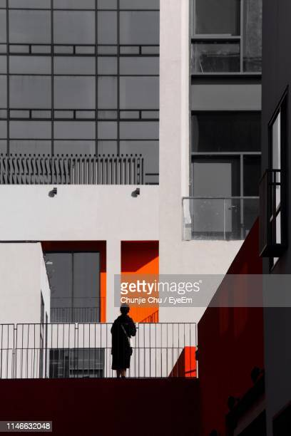 woman standing against building - isolated color stock pictures, royalty-free photos & images