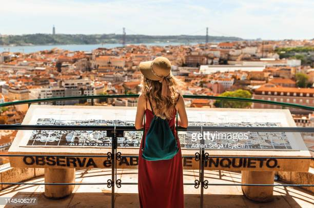 woman standing against buildings in town - lisbon stock pictures, royalty-free photos & images