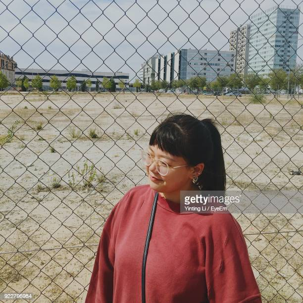 Woman Standing Against Chainlink Fence