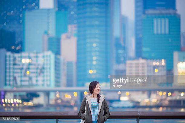 Woman standing against city skyline with smile