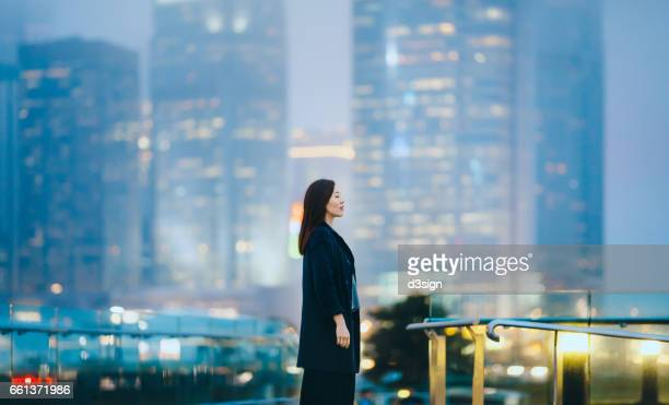 Woman standing against commercial city skyline enjoying the tranquility with her eyes closed