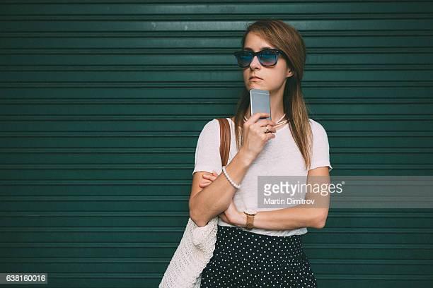 woman standing against green wall - ongeduldig stockfoto's en -beelden