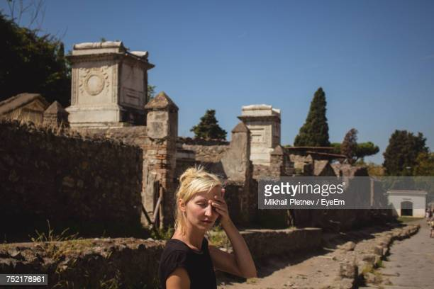 woman standing against historic building at pompeii during sunny day - ancient civilization stock pictures, royalty-free photos & images