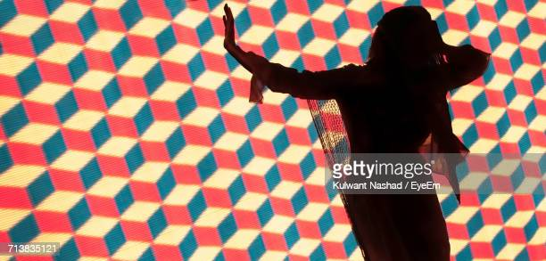 Woman Standing Against Illuminated Background With Geometric Pattern