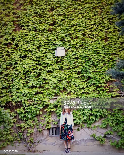 woman standing against ivy covered wall - edera foto e immagini stock