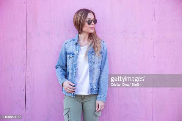 woman standing against pink wooden wall - straight hair stock pictures, royalty-free photos & images