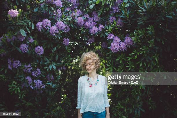 Woman Standing Against Purple Flowering Plants