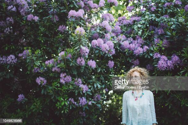 woman standing against purple flowering plants - bortes stockfoto's en -beelden