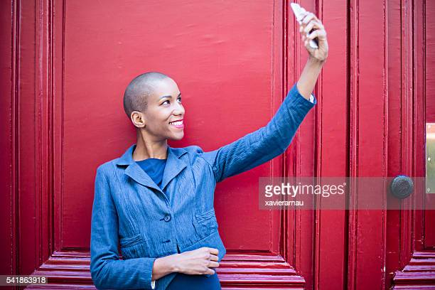 Woman standing against red door taking self portrait.