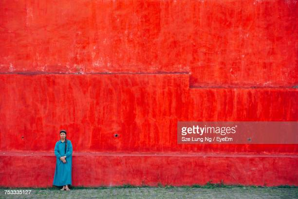 Woman Standing Against Red Wall