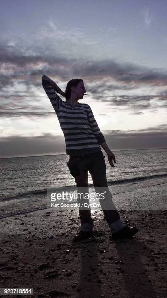 Woman Standing Against Sea During Sunset