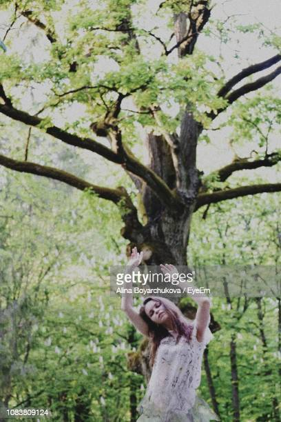 Woman Standing Against Tree Trunk