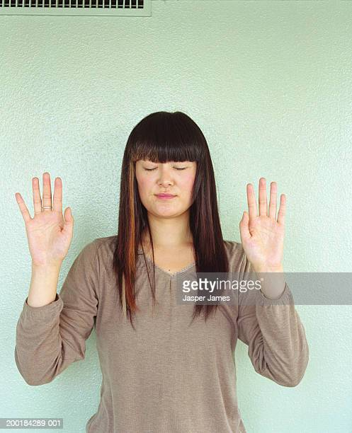 Woman standing against wall with hands raised, eyes closed