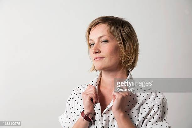 Woman standing against white background, smiling, portrait