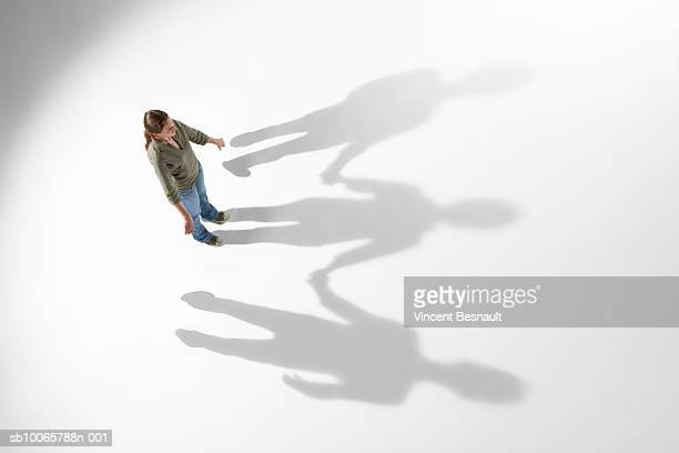 Woman standing alone, shadow showing holding hands with people