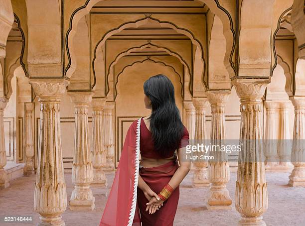 woman standing amid columns - sari stock pictures, royalty-free photos & images