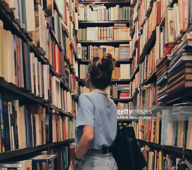 Woman Standing Amidst Books In Store