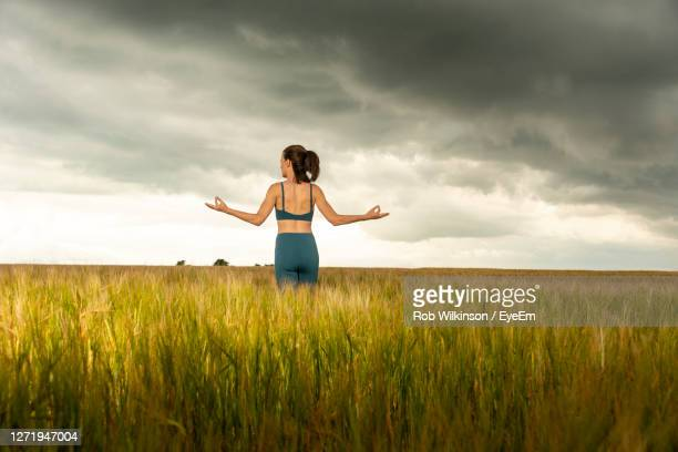 woman standing amidst field against sky - portsmouth england stock pictures, royalty-free photos & images