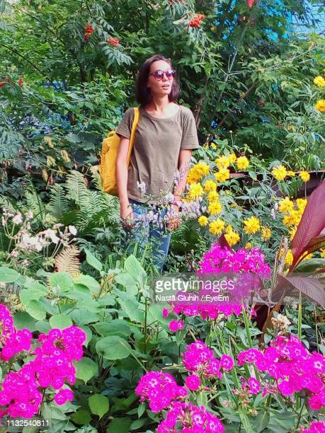 woman standing amidst flowers at park - nizhny novgorod oblast stock photos and pictures