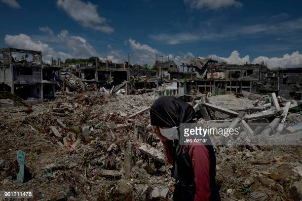 A woman standing amidst the destruction inside Marawi city on May 10 2018 in Marawi Philippines With their homes destroyed and their properties...