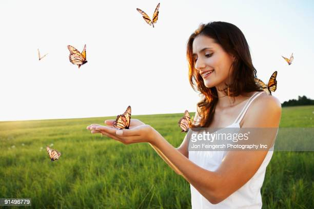 woman standing among butterflies in meadow - schmetterling stock-fotos und bilder