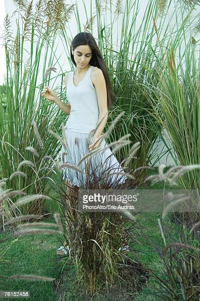 'Woman standing among long grasses and reeds, full length'