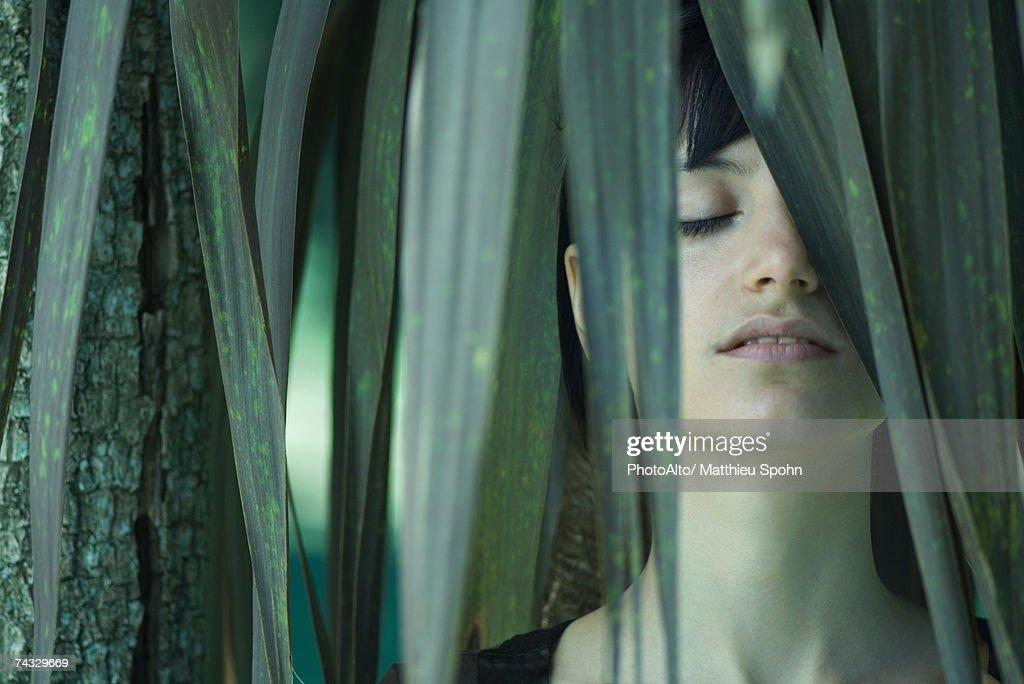 Woman standing among palm leaves, eyes closed : Bildbanksbilder